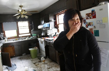 PHOTO #6. Mei Zhu surveys damage to her home in Sayerville. Photo: Star Ledger